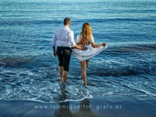 Foto de postboda atrevida y original con novios en la playa entrando en el agua