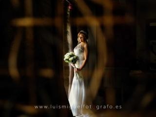 La novia mirando su ramo en su habitación saliendo para la ceremonia