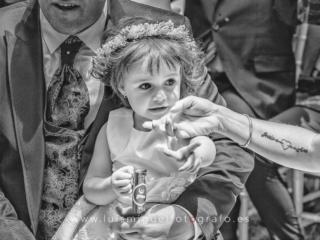 Niña de los novios acariciada por la novia durante la ceremonia de la boda