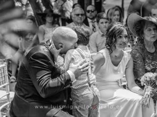 Niño de los novios acariciada por la novia durante la ceremonia de la boda