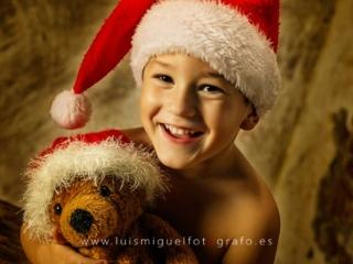 Niño sonriendo con osito de papa noel