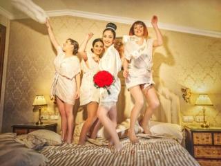 Novia con damas de honor saltando en la cama