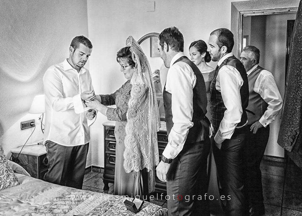 Familia vistiendo al novio antes de la boda