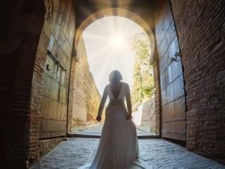 foto de postboda con novia en la puerta de la alhambra iluminada por los rayos del sol