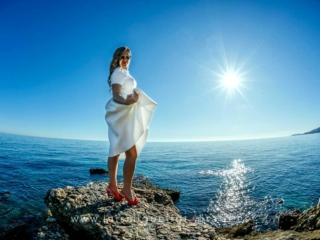 foto de postboda con novia sobre el horizonte azul del mar