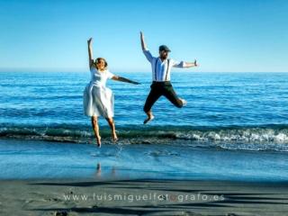 foto de postboda con novios saltando en la orilla de la playa