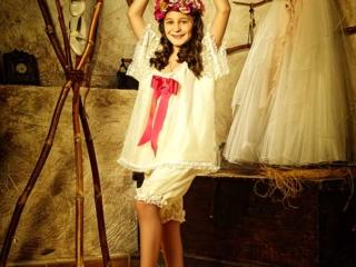 niña de comunión junto a su vestido