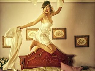 Novia salta divertida antes de ponerse el vestido de su boda